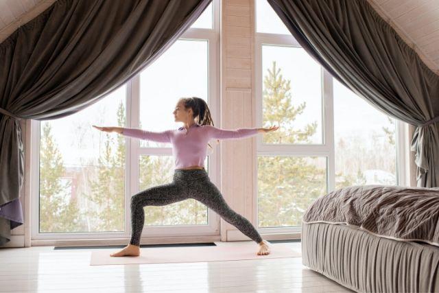 Dziewczyna z dredami wykonuje w domu ćwiczenia na plecy. Stoi na macie, obok dużego okna.