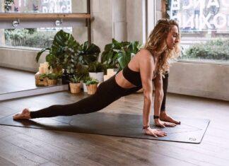 Dziewczyna w stroju do fitnessu wykonuje na macie ćwiczenia na plecy. Ma długie blond włosy.