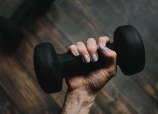 Czarny hantel w kobiecej dłoni na tle drewnianej podłogi. Takie przyrządy przydają się, jeśli chcesz wykonywać ćwiczenia w domu.