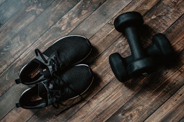 Czarne adidasy i dwa hantle leżą na drewniane podłodze. To atrybuty potrzebne do ćwiczenia w domu.
