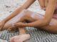 Dziewczyna w pastelowym kostiumie kąpielowej smaruje nogi kremem z SPF.