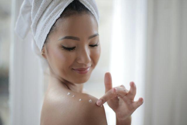 Dziewczyna w białym ręczniku na głowie, które smaruje ramię kremem z SPF.