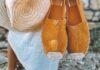 Espadryle w kolorze camel, które trzyma w ręku kobieta w białej sukience i z kapeluszem w drugiej dłoni.