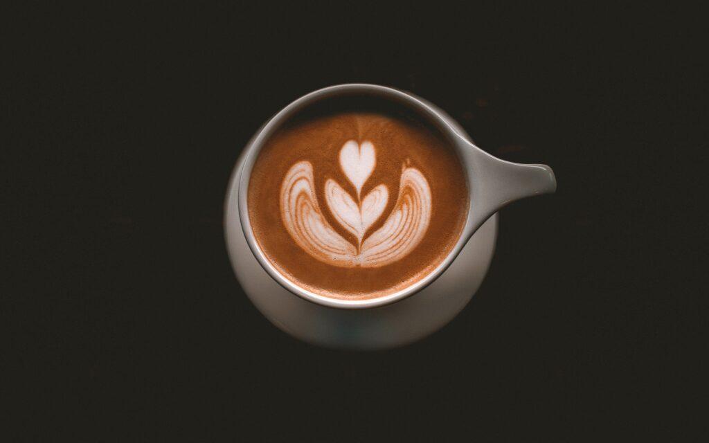 Kawa ze spienionym mlekiem i wzorkiem podana w białej filiżance na białym spodku.