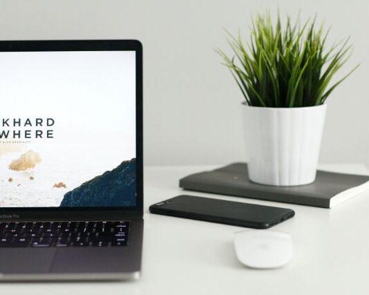 Na białym biurku znajdują się: komputer, myszka, telefon i kwiatek. To przedmioty, które często można znaleźć na biurku freelancera.