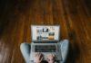 Młody chłopak, który siedzi na drewnianej podłodze z laptopem na kolanach i pracuje jako freelancer.