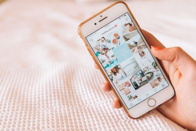 Influencer to wymarzona praca dla młodych ludzi. Na zdjęciu widać telefon z otwartą aplikacją social mediową, która pokazuje, jak pracuje influencer.