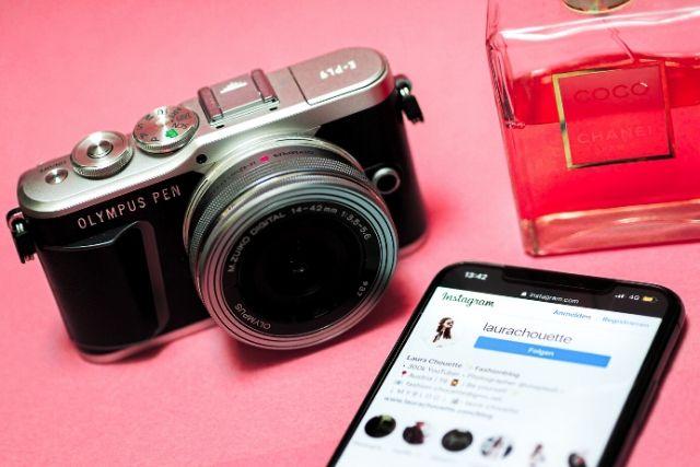 Influencer pracuje przede wszystkim, dodając zdjęcia i rekomendując produkty. Na zdjęciu aparat, telefon z otwartą aplikacją social mediową i flakon perfum.