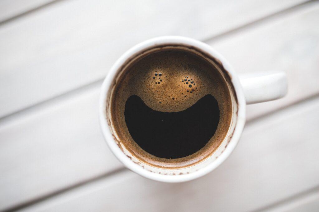 Nie jest łatwo odpowiedzieć na pytanie, czy kawa jest zdrowa. Biały kubek z kawą, której pianka układa się w uśmiech.