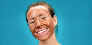 Domowa maseczka na twarz w kolorze brązowym. Usmiechnięta kobieta ze spiętymi, brązowymi włosami i maseczką na twarzy.