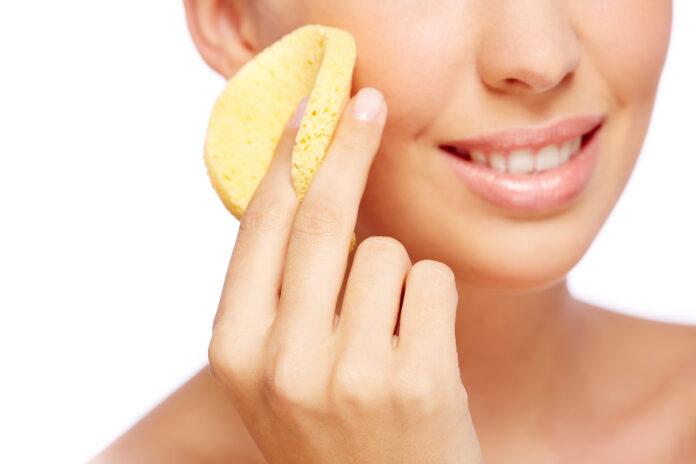 Młoda kobieta trzymająca w dłoni okrągłą żółtą gąbkę i lekko uśmiechnięta