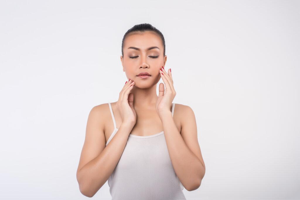 Kobieta ze związanymi włosami, dotyka dłońmi twarzy. Domowy peeling do twarzy pozwala na uzyskanie gładkiej i jędrnej cery.