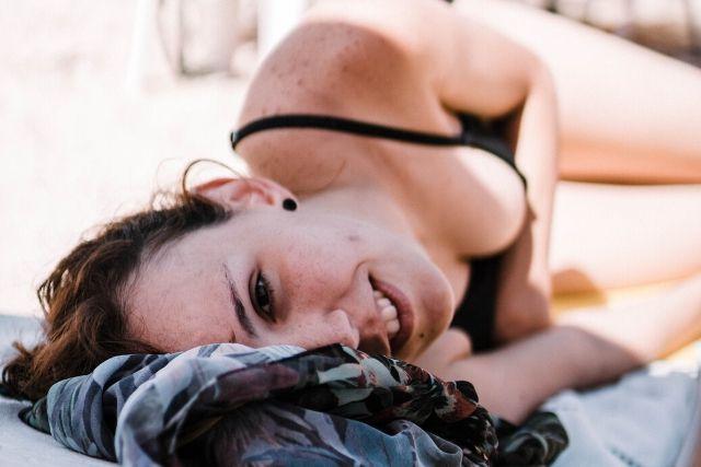 Dziewczyna opalająca się na plaży w czarnym stroju kąpielowym, leży na boku i patrzy w obiektyw. Na skórze ma widoczne przebarwienia spowodowane promieniowaniem UV.