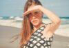 Młoda dziewczyna, z długimi włosami zasłania oczy przed słońcem. Stoi na plaży i ma na sobie kostium kąpielowy w biało-czarny geometryczny wzór. Opalanie jest skutkiem, jaki wywołuje promieniowanie UV.