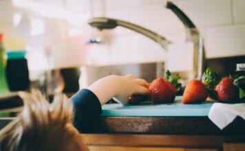 Przekąski dla dzieci w postaci truskawek leżących na blacie