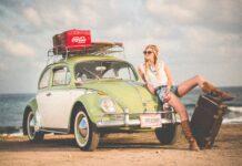 Styl boho w modzie: młoda dziewczyna z blond włosami siedzi na masce samochodu garbus nad brzegiem morza.