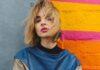 Młoda dziewczyna, pracująca jako szafiarka, stojąca na tle kolorowej ściany.