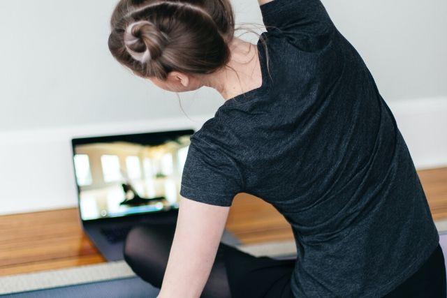 Młoda dziewczyna, ubrana na czarno, która realizuje swój trening w domu. Siedzi na macie i ćwiczy wspólnie z trenerką internetową.