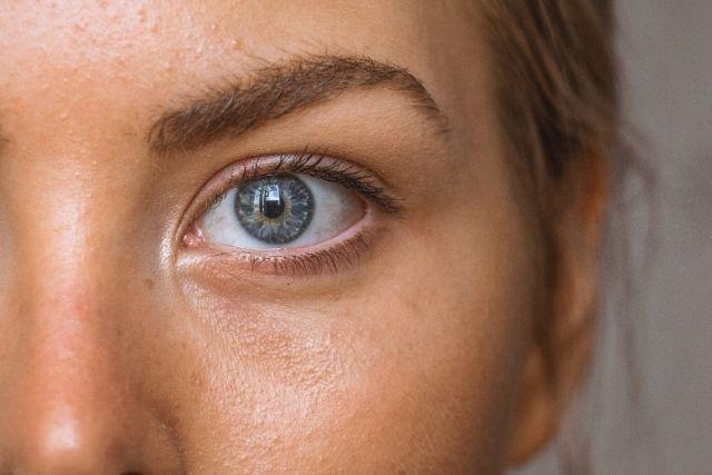 Duże zbliżenie na twarz młodej kobiety i jej niebieskie obok. WIdać delikatne worki pod oczami.