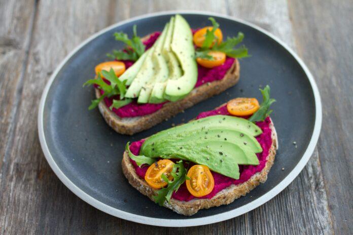 Zdrowe przekąski w postaci chleba posmarowanego czerwonym hummusem z avocado i żółtymi pomidorkami na wierzchu.