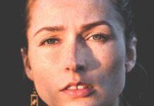 Zmarszczki na czole delikatnie zarysowane na twarzy młodej dziewczyny, patrzącej prosto w obiektyw przy świetle zachodzącego słońca.