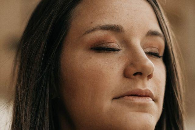 Zmarszczki na czole widoczne na twarzy młodej dziewczyny o brązowych włosach i delikatnie umalowanych, zamkniętych oczach.