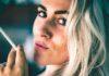 Blondynka z ciemnymi brwiami i niebieskimi oczami, która ma twarzy widoczne zmarszczki palacza i trzyma w dłoni papierosa.