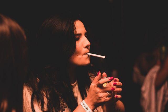 Brunetka z papierosem w ustach, którego chce odpalić. Na twarzy widać tzw. zmarszczki palacza.