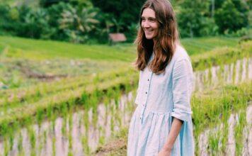 Przykład tego, jak wygląda ekologiczna moda. Młoda dziewczyna ubrana w lnianą sukienkę, z rozpuszczonymi, brązowymi włosami stoi na tle zieleni i małej rzeki.