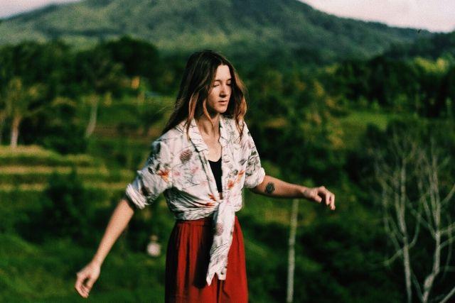 Ekologiczna moda powstaje z przyjaznych planecie materiałów. Na zdjęciu młoda dziewczyna z rozpuszczonymi włosami, która idzie przez górzysty, zielony teren.