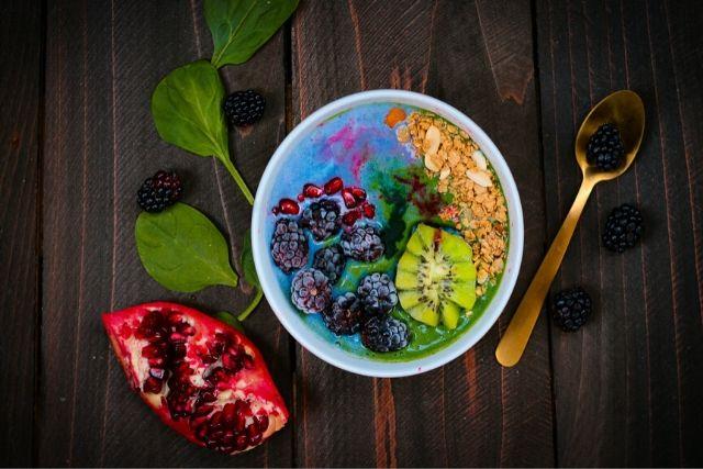 Miska owoców, obok niej liście szpinaku, połówka granatu i złota łyżeczka. Ilustracja tego na temat tego, jak fruktoza wpływa na odchudzanie.
