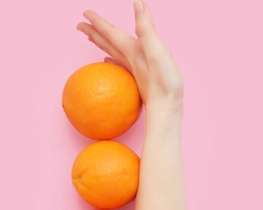 Kobieca ręka odgradzająca pomarańczowe, na różowym tle. Ilustracja dotycząca tego, jak fruktoza wpływa na utrzymanie prawidłowej wagi.