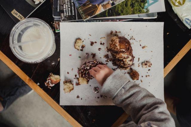 Dziecięca rączka sięgająca po słodycze leżące na stole. Jeśli zastanawiasz się, czym zastąpić słodycze w diecie dziecka, zacznij od wprowadzania owoców.