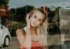 Młoda dziewczyna o blond włosach, która ma na głowie duże słuchawki. Zdjęcie zrobione przez szybę. Ilustracja artykułu o tym, jaka powinna być muzyka do pracy.
