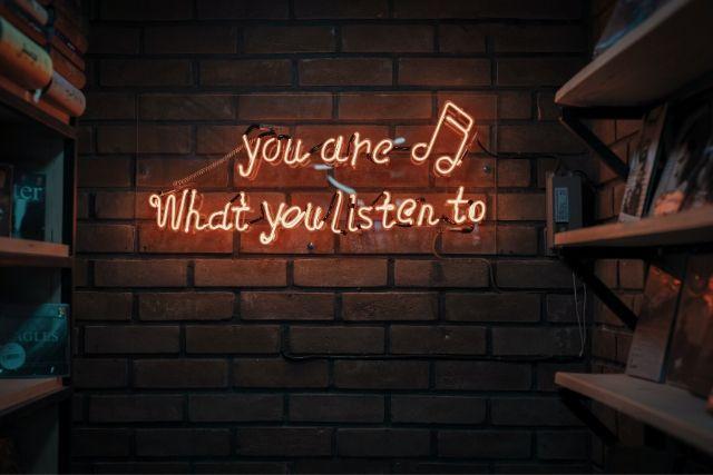 Neonowy napis na ceglanej ścianie: you are what you listen to. Ilustracja artykułu o tym, jaka powinna być muzyka do pracy.