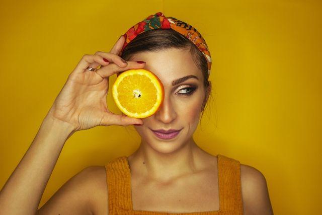 Czy nadmiar witaminy C w organizmie w ogóle jest możliwy? Na zdjęciu młoda dziewczyna, która plastrem pomarańczy zasłania jedno oko. Stoi na tle żółtej ściany.