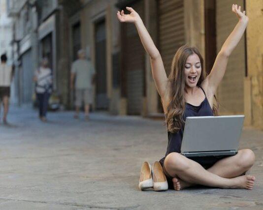 Młoda dziewczyna, która siedzi boso na deptaku z komputerem na kolanach. Obok niej stoją jej szpilki. Ma wyciągnięte do góry ręce i jest usmiechnięta. Produktywność jest kluczem do sukcesu zawodowego.