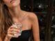 Młoda dziewczyna, z długimi blond włosami, w czarnej koszulce bez ramiączek pije wodę. To przykład tego, jak mogą wyglądać zdrowe rytuały.