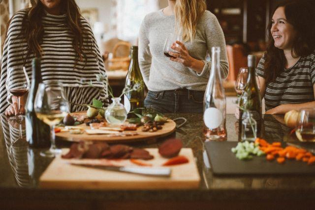 Rytuały zdrowego spożywania posiłków warto rozpocząć od wspólnego siadania do stołu. Na zdjęciu trzy kobiety, które wspólnie spędzają czas przy posiłku.