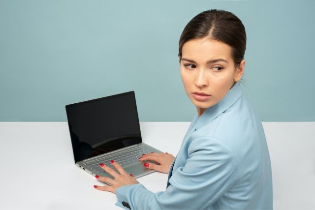 Młoda kobieta z upiętymi włosami siedzi przy biurku przed komputerem. Na jej twarzy maluje się stres.