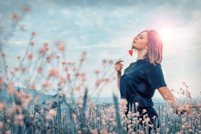Dziewczyna z krótko obciętymi włosami na łące pełnej kwiatów. Kontakt z naturą to jeden ze sposobów na to, jak pokonać stres.