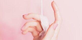 Kobieca dłoń na różowym tle, na którą leje się emulsja nawilżająca. Grafika ilustrująca problem, jakim są suche dłonie.