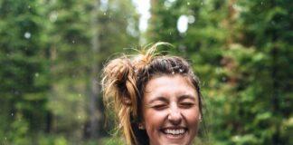 Uśmiechnięta młoda dziewczyna odczuwająca szczęście. Ma spięte w kok włosy, a za jej plecami widać las.
