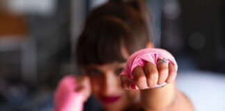 Trening obowodowy to dobry sposób na to, jak pozostac w formie, nawet kiedy nie można skorzystać z siłowni. Na zdjęciu dziewczyna w różowych rękawiczkach do trningu ćwiczy wyprowadzanie ciosu.