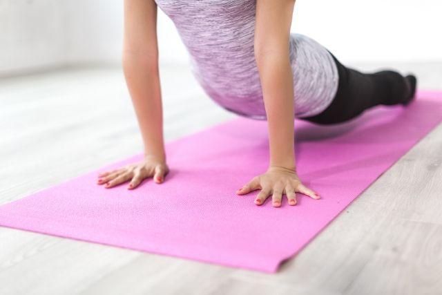 Trening obwodowy w domu wykonywany na macie. Kobieta na różwej macie do ćwiczeń wykonuje ćwiczenie na plecy i ręce.
